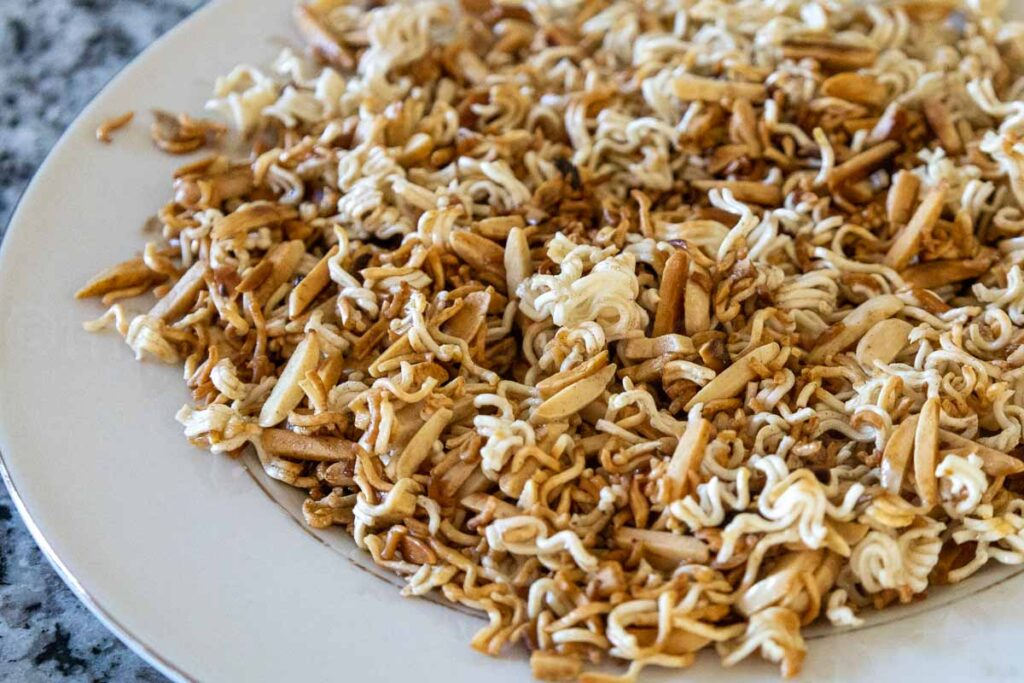 Upclose image of golden toasted ramen and slivered almonds in a cream color bowl.