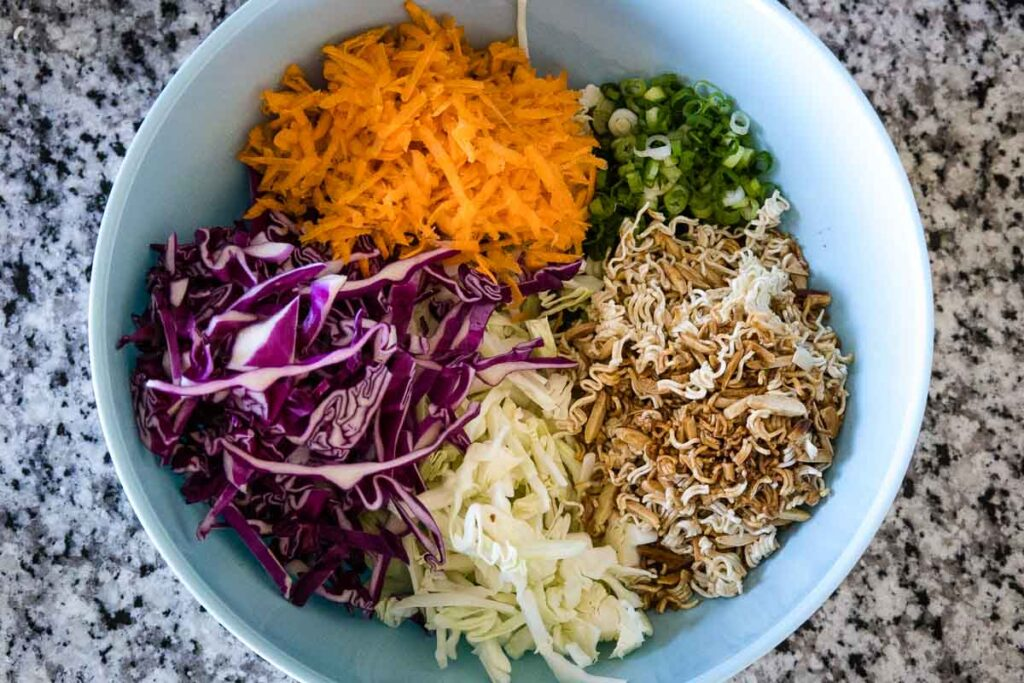 A large mixing bowl with a blue interior holding from 12:00 going clockwise, shredded carrots, chopped green onions, toasted almond and ramen noodles, green cabbage, and purple cabbage.