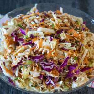 A clear crystal bowl full of Ramen Noodle Salad with shredded green and red cabbage, shredded carrots, toasted ramen noodles and almond.