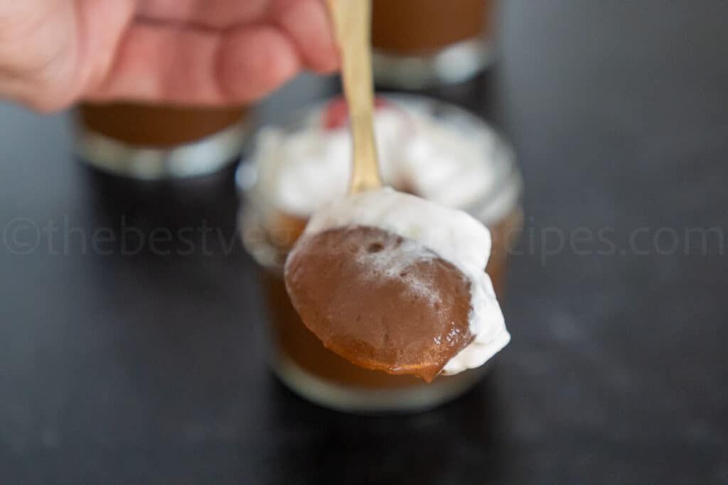 A gold spoonful of chocolate avocado pudding and whipped topping with the jar of pudding blurred in the background