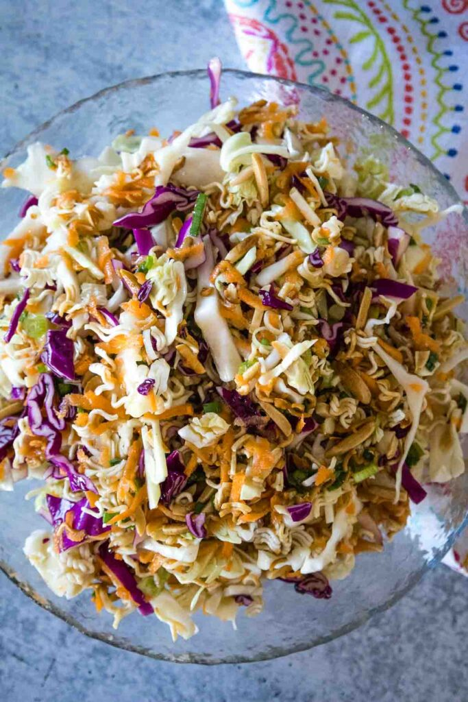 Overhead upclose shot of Ramen Noodle Salad in a clear glass bowl with flecks of purple cabbage, shredded carrots, green cabbage, green onions, and toasted ramen noodles with slivered almonds mixed together.